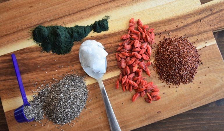 Super Food - spirulina, nasiona chia, olej kokosowy, nasiona goji na drewnianej desce